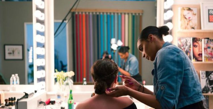 stylist in studio doing hair and makeup with client